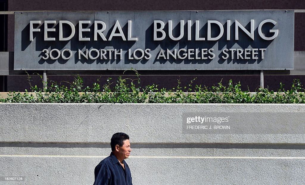 A pedestrian walks past a federal building in Los Angeles where immigration services remained open but not the office of the Internal Revenue Service, frustrating those who arrived only to find services closed, on October 1, 2013 in Los Angeles, California. US monuments closed, offices fell silent and 800,000 public servants were told to stay at home on Tuesday as Washington's perennial political crisis forced the first government shutdown in 17 years. AFP PHOTO/Frederic J. BROWN