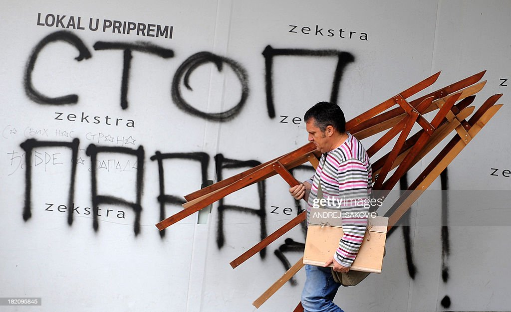 A pedestrian walks past a graffiti that reads 'Stop to the Pride Parade' in Belgrade on September 28, 2013. Hundreds of police were on the streets of Belgrade Saturday after authorities banned Gay Pride for the third year running, an act the EU said was regrettable.