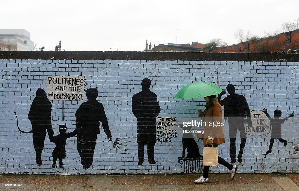 A pedestrian walks past a graffiti-covered brick wall in London, U.K., on Thursday, Dec. 20, 2012. Britain's economy expanded less than previously estimated in the third quarter and the budget deficit unexpectedly widened in November, complicating Prime Minister David Cameron's attempts to bolster the recovery. Photographer: Simon Dawson/Bloomberg via Getty Images