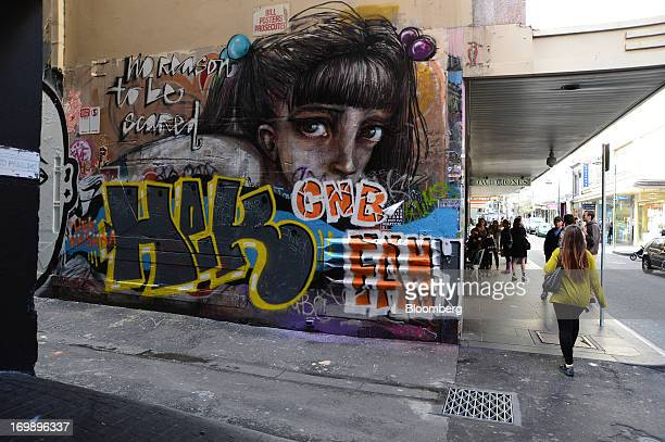 A pedestrian walks past a graffiticovered laneway wall on the facade of a David Jones Ltd department store in central Melbourne Australia on Sunday...