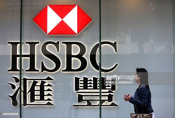 A pedestrian walks past a HSBC sign in Hong Kong on November 2 2015 HSBC saw pretax profit surge 32 percent year on year in the third quarter the...