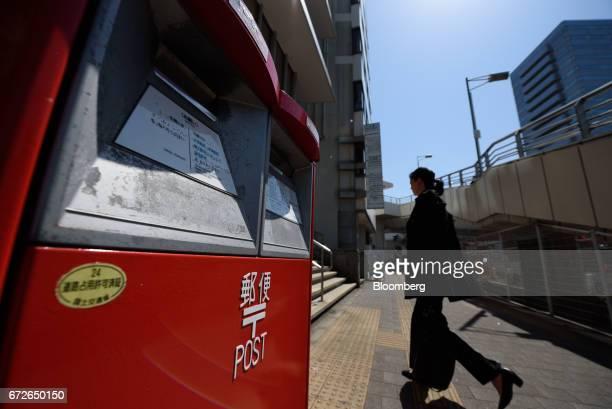 A pedestrian walks past a Japan Post Co mail box in Kawasaki Kanagawa Prefecture Japan on Tuesday April 25 2017 Japan Post Holdings Co Ltdwill book...