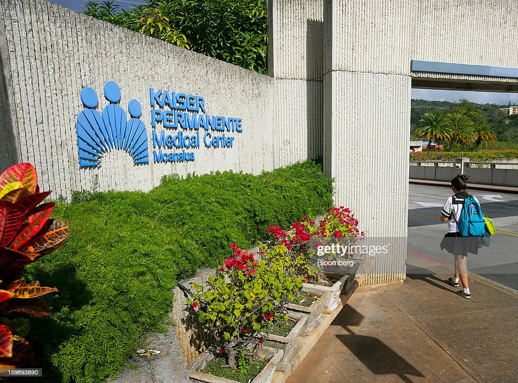 A pedestrian walks past a Kaiser Permanente Hawaii Medical Center signage in Honolulu, Hawaii, U.S., on Wednesday, Jan. 9, 2013. Honolulu, the southernmost major U.S. city, is a major financial center of the islands of the Pacific Ocean. Photographer: Tim Rue/Bloomberg via Getty Images