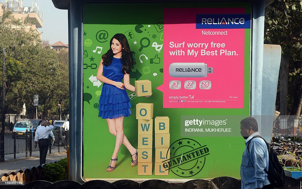 A pedestrian walks past a kiosk with an advertisement for Reliance Communications in Mumbai on January 16, 2013. Indian mobile phone company Reliance Communications will award a $1-billion, eight-year contract to US-French telecom equipment supplier Alcatel-Lucent, the companies said Wednesday. The contract plans to deliver voice and data communication services to RCom's networks in southern and eastern India, they said in a statement. The deal, which will see nearly 4,000 RCom employees -- 15 percent of its workforce -- move to Alcatel, comes at a time when local telecom firms have been slowing down investments, amid intense competition and regulatory policy uncertainty in India, one of the world's largest telecom markets.