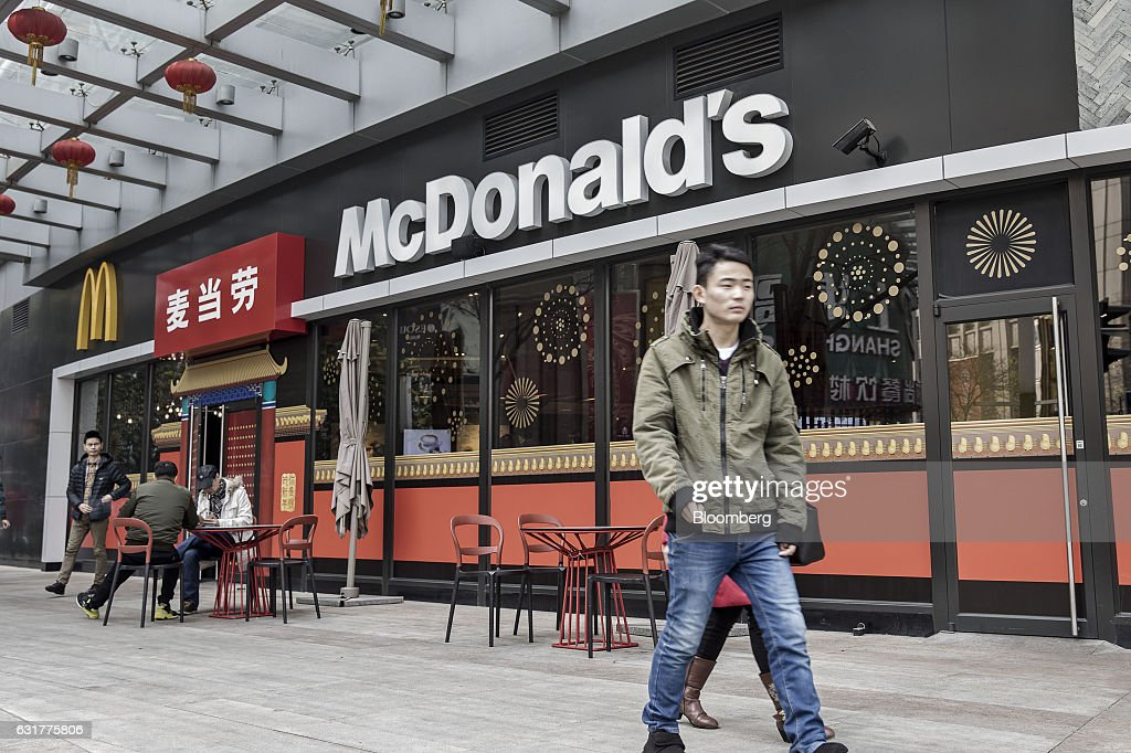 A pedestrian walks past a McDonald's Corp. restaurant in Shanghai, China, on Friday, Jan. 13, 2017. McDonald's agreed to sell a controlling stake in its China and Hong Kong operations to a group of investors for about $1.7 billion, a key component of the fast-food giants reorganization in a market where its striving to catch up with more nimble rivals. Photographer: Qilai Shen/Bloomberg via Getty Images