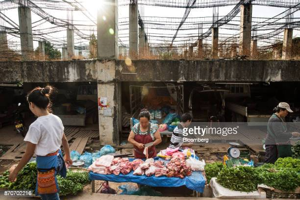 A pedestrian walks past a meat vendor at a morning market in Vientiane Laos on Thursday Nov 2 2017 Located in the Mekong region Southeast Asia's...