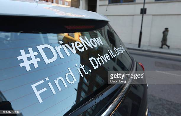 A pedestrian walks past a Mini Countryman automobile part of the DriveNow carsharing venture between Bayerische Motoren Werke AG and Sixt SE in...
