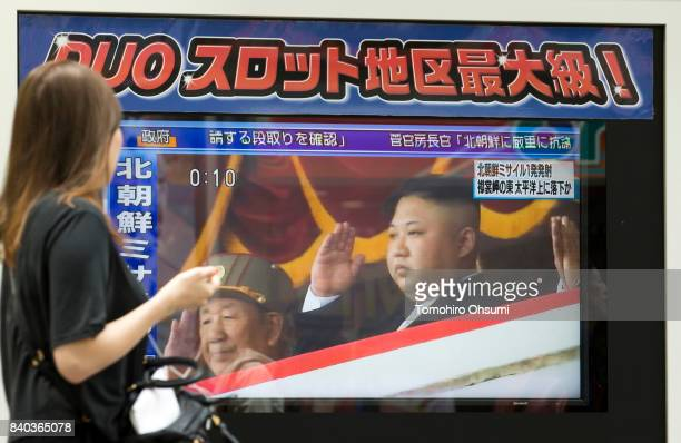 A pedestrian walks past a monitor showing an image of North Korean leader Kim JongUn in a news program reporting on North Korea's missile launch on...