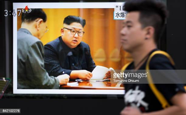 A pedestrian walks past a monitor showing an image of North Korean leader Kim JongUn in a news program reporting on North Korea's 6th nuclear test on...