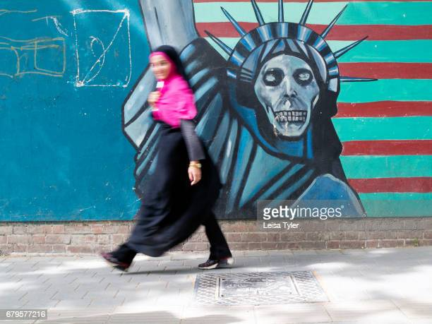 A pedestrian walks past a mural depicting the Statue of Liberty as death as painted on the wall of the former American Embassy in Tehran Iran The...