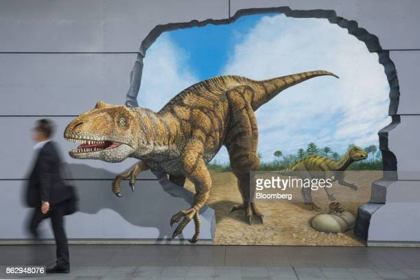 A pedestrian walks past a mural of dinosaurs outside the Fukui station in Fukui Japan on Wednesday Oct 11 2017 Fukui Prefecture has one of the lowest...