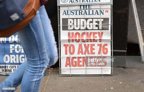 A pedestrian walks past a newspaper headline in Sydney on May 12 2014 which says the Australian Treasurer Joe Hockey will axe government jobs in his...