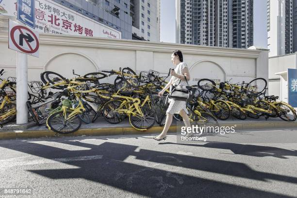 A pedestrian walks past a pile of ridesharing bicycles in Shanghai China on Thursday Sept 12 2017 Across Chinese cities sidewalks are filling up with...