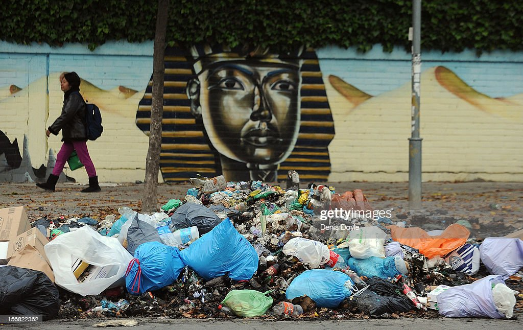 A pedestrian walks past a pile of uncollected garbage during the 21st day of the garbage collectors strike on November 22, 2012 in Jerez de la Frontera, Spain. The garbage collectors will vote today on a compromise deal which saves the 123 jobs due to be cut in favour of reductions in salaries.