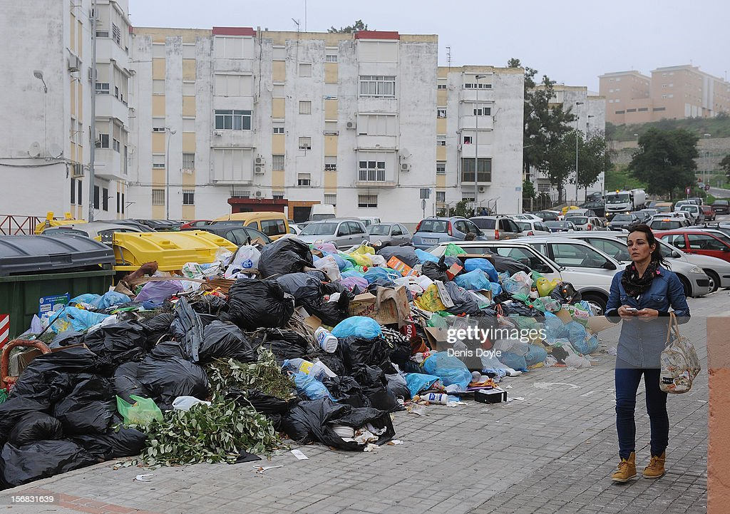 A pedestrian walks past a pile of uncollected garbage during the 21st day of the garbage collectors strike on November 22, 2012 in Jerez de la Frontera, Spain. The garbage collectors agreed on November 22nd to a compromise deal saving 123 job redundancies due to be cut in return for salary reductions.