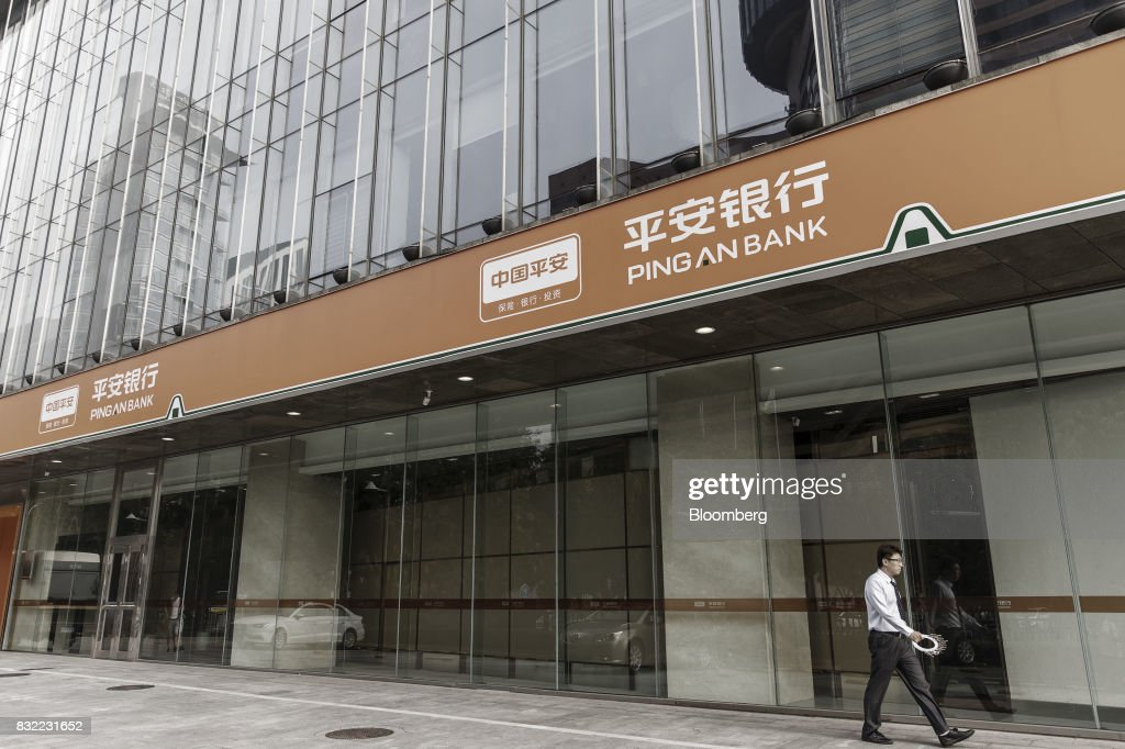 A pedestrian walks past a Ping An Bank Co. branch, a unit of PingAnInsurance Group Co., in Beijing, China, on Wednesday, Aug. 9 2017. Ping An Insurance Group is scheduled to release half year results on Aug. 17. Photographer: Qilai Shen/Bloomberg via Getty Images