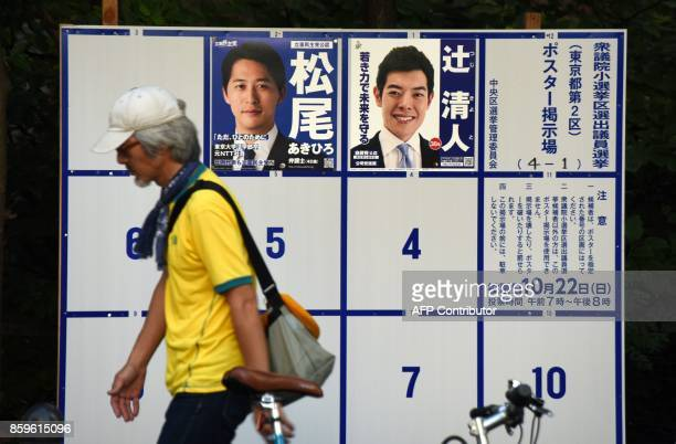 A pedestrian walks past a poster bulletin board for the lower house electoral candidates in Tokyo on October 10 2017 Tokyo's popular governor Yuriko...