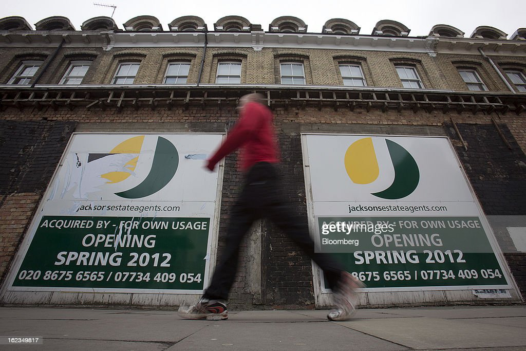 A pedestrian walks past a property advertising the future opening of a new estate agent office in the Putney district of London, U.K., on Friday, Feb. 22, 2013. U.K. home sellers raised their asking prices to the most for a February in five years as inquiries from potential buyers increased, Rightmove Plc said. Photographer: Simon Dawson/Bloomberg via Getty Images