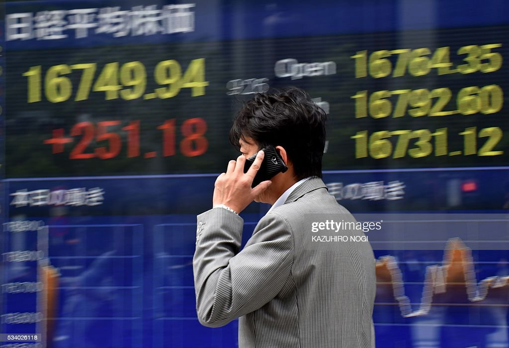 A pedestrian walks past a quotation board displaying the Nikkei key index from the Tokyo Stock Exchange in Tokyo on May 25, 2016. Tokyo stocks surged at the start of trading May 25, extending a rally on global financial markets, while Sony jumped more than five percent after investors shrugged off a weak profit forecast. / AFP / KAZUHIRO
