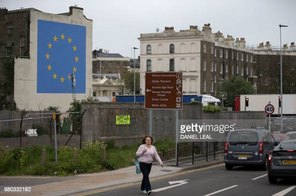 A pedestrian walks past a recently painted mural by British graffiti artist Banksy depicting a workman chipping away at one of the stars on a...