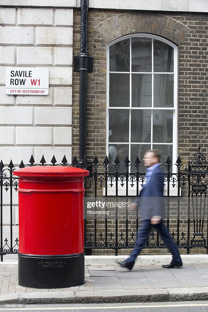 A pedestrian walks past a red Royal Mail post box as he passes commercial real estate buildings that form part of the Pollen Estate, on Savile Row in London, U.K., on Monday, Aug. 11, 2014. Norway's sovereign wealth fund, Norges Bank Investment Management, the world's largest, bought a stake in the Pollen Estate in London's Mayfair district for 343 million pounds ($576 million), expanding its property holdings in the U.K. capital. Photographer: Jason Alden/Bloomberg via Getty Images