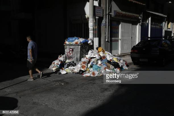 A pedestrian walks past a refuse bin overflowing with garbage on a city sidewalk during a refuse collection strikeby municipal workers in Athens...