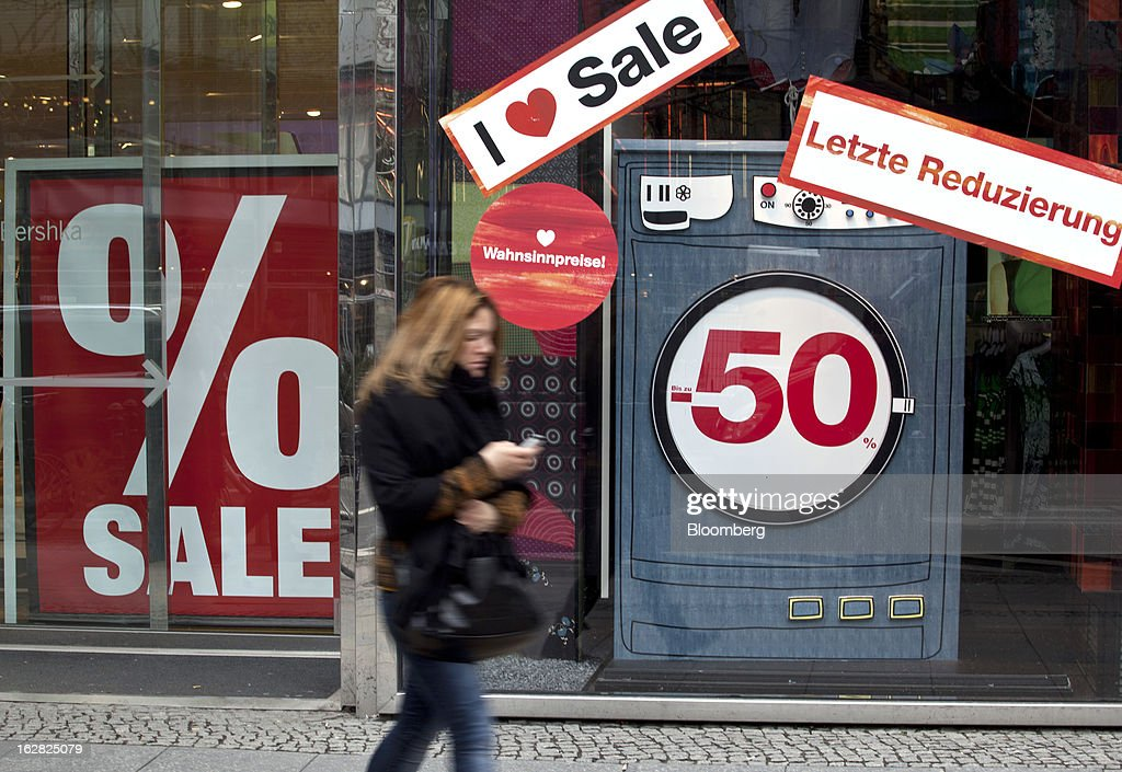 A pedestrian walks past a retail store offering sales discounts in Berlin, Germany, on Wednesday, Feb. 27, 2013. German unemployment unexpectedly fell in February amid signs that Europe's biggest economy is returning to growth after a contraction at the end of last year. Photographer: Balint Porneczi/Bloomberg via Getty Images