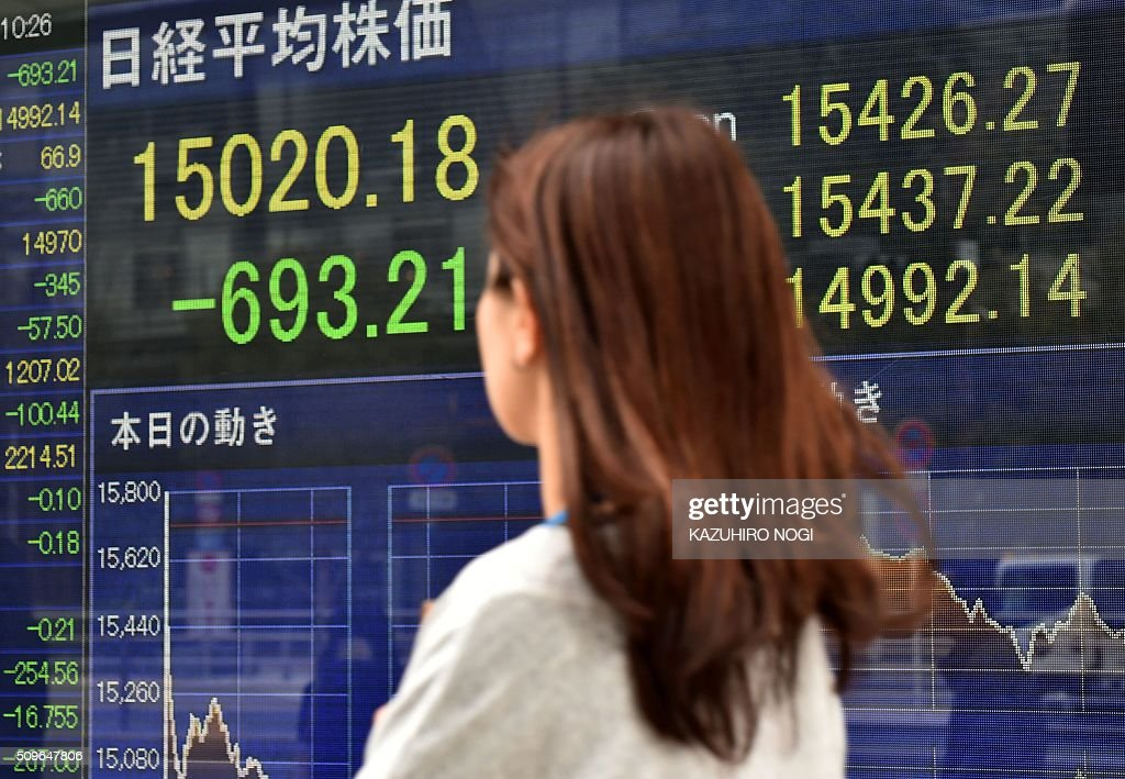 A pedestrian walks past a share prices board showing numbers of the Tokyo Stock Exchange in Tokyo on February 12, 2016. Tokyo stocks tumbled more five percent in early deals on February 12, playing catch-up with a global sell-off after a one-day holiday amid deepening worries about the world economy and as a stronger yen hammered exporters. AFP PHOTO / KAZUHIRO NOGI / AFP / KAZUHIRO NOGI