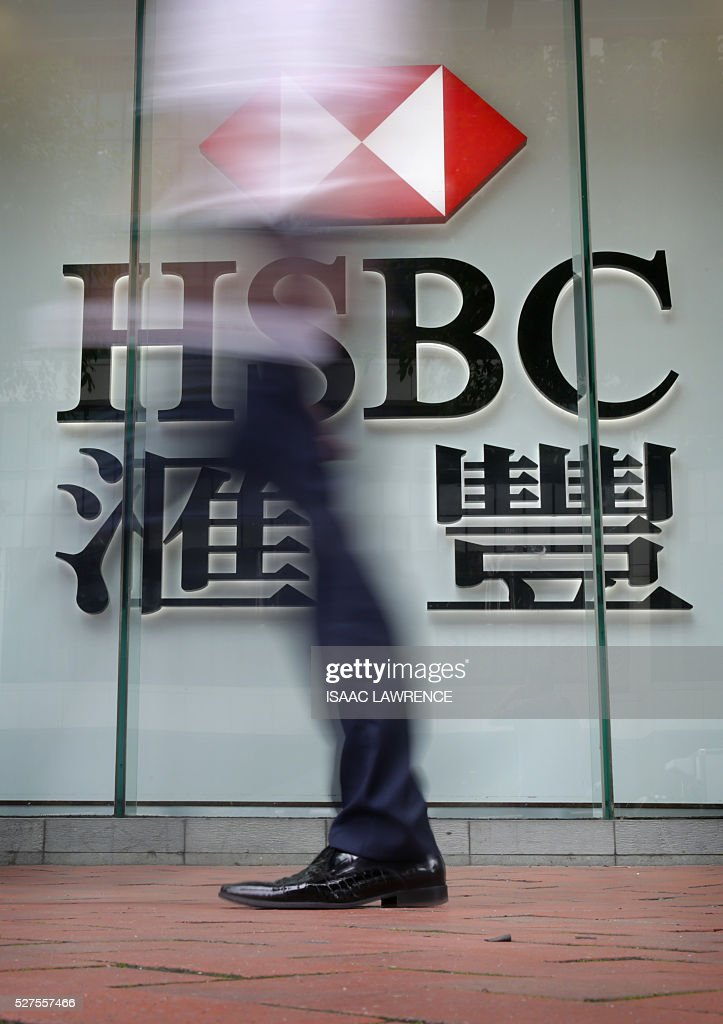 A pedestrian walks past a sign for the Hong Kong and Shanghai Banking Corporation (HSBC) bank in Hong Kong on May 3, 2016. HSBC's net profit was down 18 percent at 4.3 billion USD in the first quarter, the bank said on May 3, affected by 'extreme levels' of market volatility early in the year. LAWRENCE