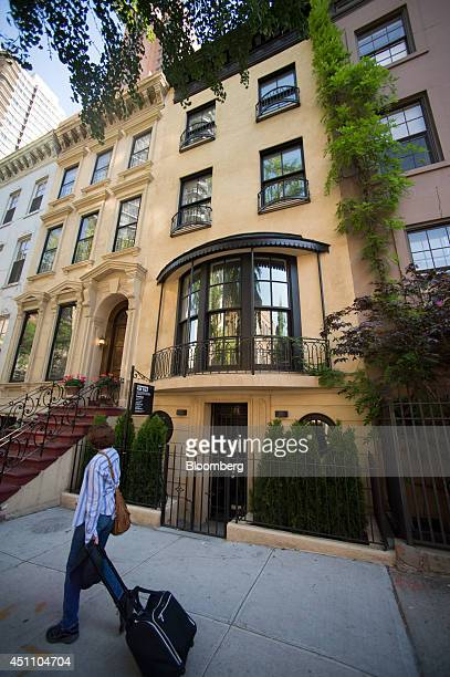 A pedestrian walks past a Sotheby's 'For Sale' sign displayed outside of a townhouse in New York US on Monday June 23 2014 Americans snapped up...