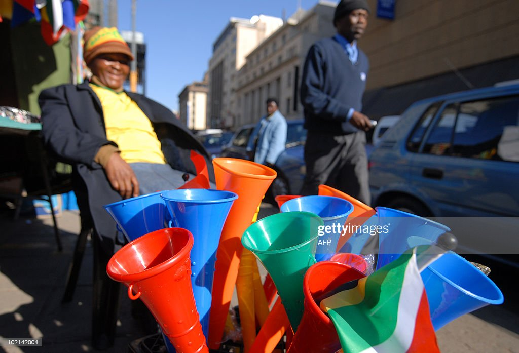 A pedestrian walks past a South African roadside vendor (L) selling vuvuzela horns along a street in Pretoria on June 16, 2010 just hours before the 2010 World Cup football match between South Africa and Uruguay in the city. London mayor Boris Johnson said on June 16 while visiting Cape Town that the vuvuzela trumpets likely would not figure in the 2018 World Cup if England wins its bid to host it, comparing the noise to a 'mosquito in your ear'. AFP PHOTO / Monirul Bhuiyan