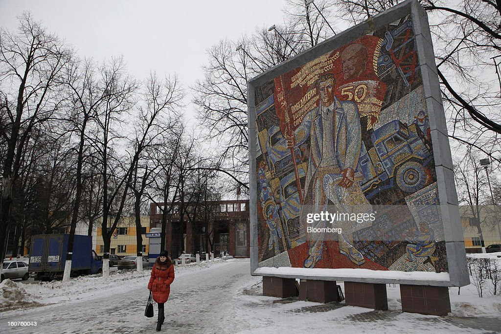 A pedestrian walks past a Soviet-era mosaic artwork outside the entrance to the GAZ Group automobile plant in Niznhy Novgorod, Russia, on Tuesday, Feb. 5, 2013. GAZ, which is controlled by Russian billionaire Oleg Deripaska, plans to make 30,000 Aveo sedans and hatchbacks a year at its plant in Nizhny Novgorod starting in mid-2012. Photographer: Alexander Zemlianichenko Jr./Bloomberg via Getty Images