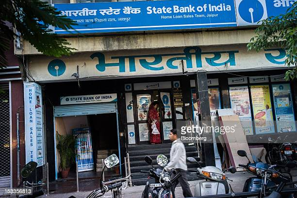 A pedestrian walks past a State Bank of India branch in Jaipur Rajasthan India on Wednesday Oct 3 2012 The Indian economy will expand 56 percent in...