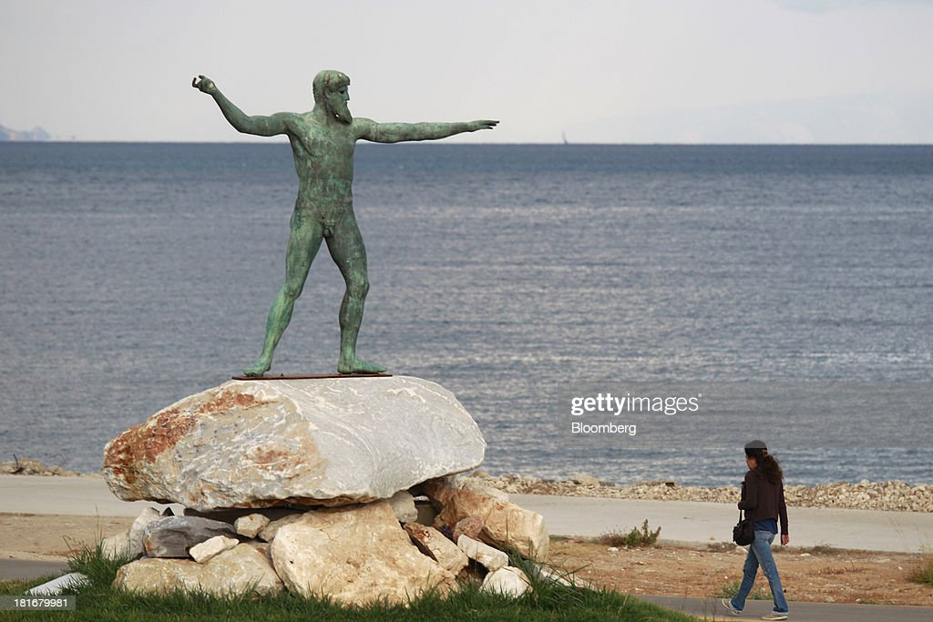 A pedestrian walks past a statue of the ancient Greek God Poseidon on the waterfront in Corinth, Greece, on Monday, Sept. 23, 2013. While the country's lenders are on firmer footing after getting capital from euro-area and International Monetary Fund bailout funds, they still need to reduce the non-performing loans that have tripled to 29 percent of the total in three years and threaten their new-found solvency. Photographer: Kostas Tsironis/Bloomberg via Getty Images