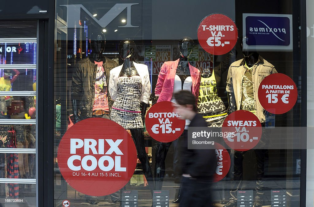 A pedestrian walks past a store offering sales discounts in its window display in Brussels, Belgium, on Monday, May 13, 2013. Euro-area data this week will probably reveal economic scars of the sovereign debt crisis confirming that the region is now suffering the longest recession since the single currency's creation. Photographer: Jock Fistick/Bloomberg via Getty Images