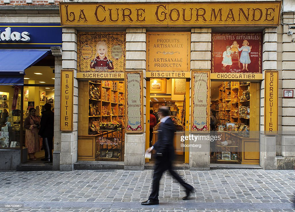 A pedestrian walks past a store on the Grand Place specialising in Belgian confectionary in Brussels, Belgium, on Monday, May 13, 2013. Euro-area data this week will probably reveal economic scars of the sovereign debt crisis confirming that the region is now suffering the longest recession since the single currency's creation. Photographer: Jock Fistick/Bloomberg via Getty Images