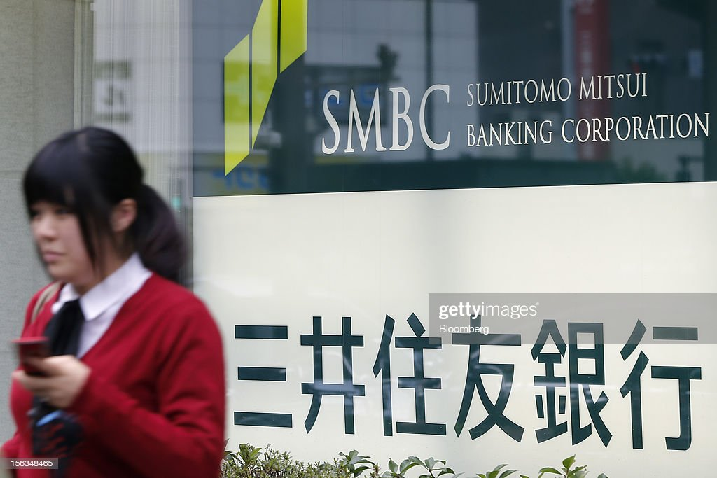 A pedestrian walks past a Sumitomo Mitsui Banking Corp. branch in Tokyo, Japan, on Tuesday, Nov. 13, 2012. Sumitomo Mitsui Financial Group Inc. is scheduled to announce first-half earnings results on Nov. 14. Photographer: Kiyoshi Ota/Bloomberg via Getty Images