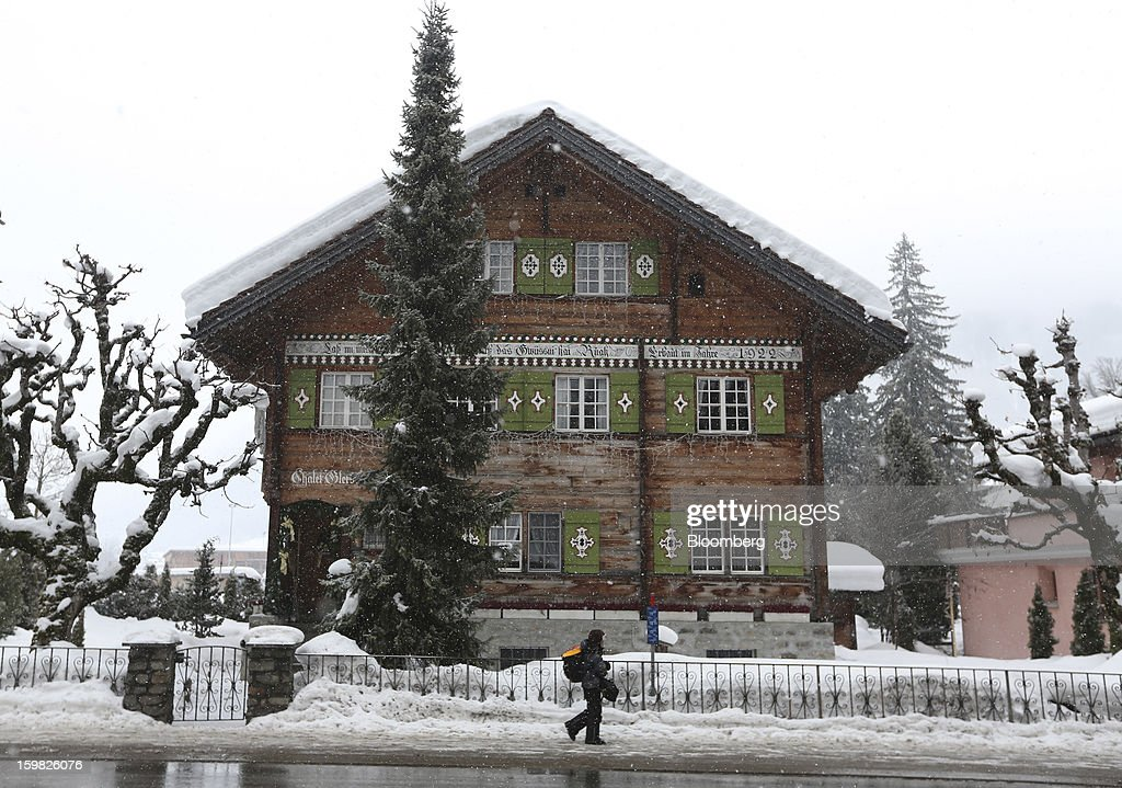 A pedestrian walks past a Swiss wooden chalet during a snow shower in Klosters, Switzerland, on Monday, Jan. 21, 2013. This week the business elite gathers in the Swiss Alps for the 43rd annual meeting of the World Economic Forum in Davos, the five day event runs from Jan. 23-27. Photographer: Chris Ratcliffe/Bloomberg via Getty Images