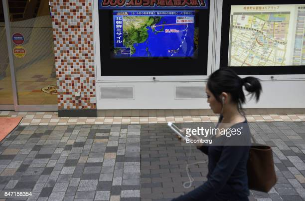 A pedestrian walks past a television screen displaying a map of Japan and the Korean Peninsula in a news program reporting on North Korea's missile...
