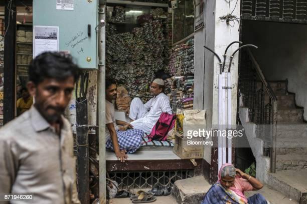 A pedestrian walks past a trader selling spools of silk thread in Varanasi Uttar Pradesh India on Saturday Oct 28 2017 In Varanasi where the...