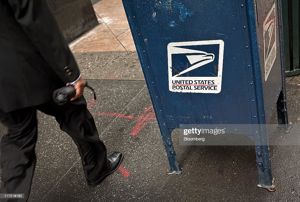 A pedestrian walks past a U. S. Postal Service mailbox in New York, U.S., on Thursday, June 23, 2011. The U.S. Postal Service, facing insolvency without approval to delay a $5.5 billion payment for worker health benefits, will suspend contributions to an employee retirement account to save $800 million this year. Photographer: Timothy Fadek/Bloomberg via Getty Images