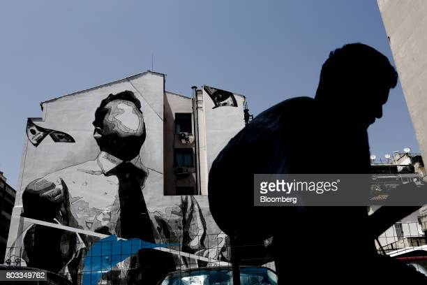 A pedestrian walks past a wall mural by visual artist 'Ino' in Athens Greece on Thursday June 29 2017 The change in sentiment toward Greece the...