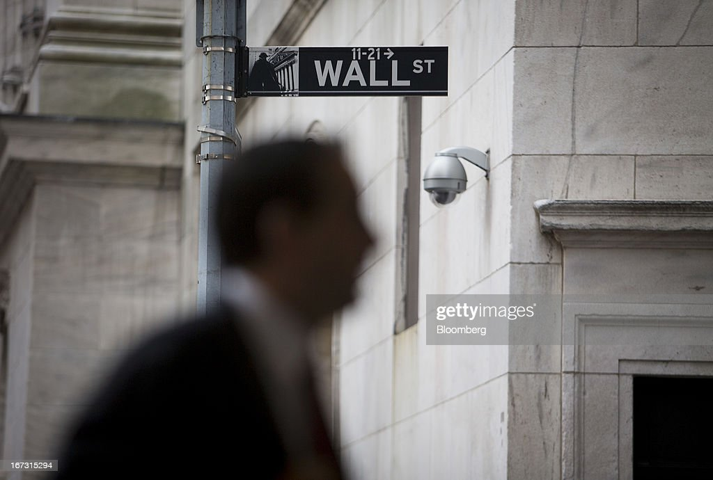 A pedestrian walks past a Wall Street sign and security camera in front of the New York Stock Exchange (NYSE) in New York, U.S., on Wednesday, April 24, 2013. U.S. stocks were little changed, after the Standard & Poor's 500 Index gained for a third day, as investors watched earnings at companies from Boeing Co. to Apple Inc. Photographer: Scott Eells/Bloomberg via Getty Images
