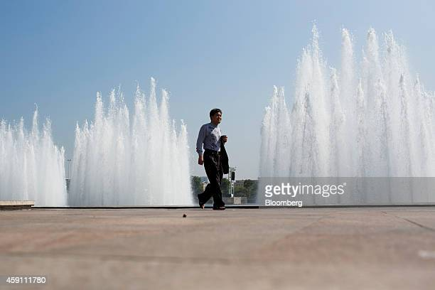 A pedestrian walks past a water fountain in Zhuhai Guangdong province China on Saturday Nov 15 2014 Investors piled into Shanghai shares on the first...