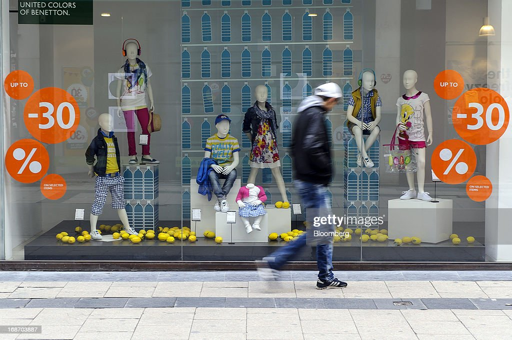 A pedestrian walks past a window display offering sales discounts at the United Colors of Benetton store, operated by Benetton Group SpA, in Brussels, Belgium, on Monday, May 13, 2013. Euro-area data this week will probably reveal economic scars of the sovereign debt crisis confirming that the region is now suffering the longest recession since the single currency's creation. Photographer: Jock Fistick/Bloomberg via Getty Images