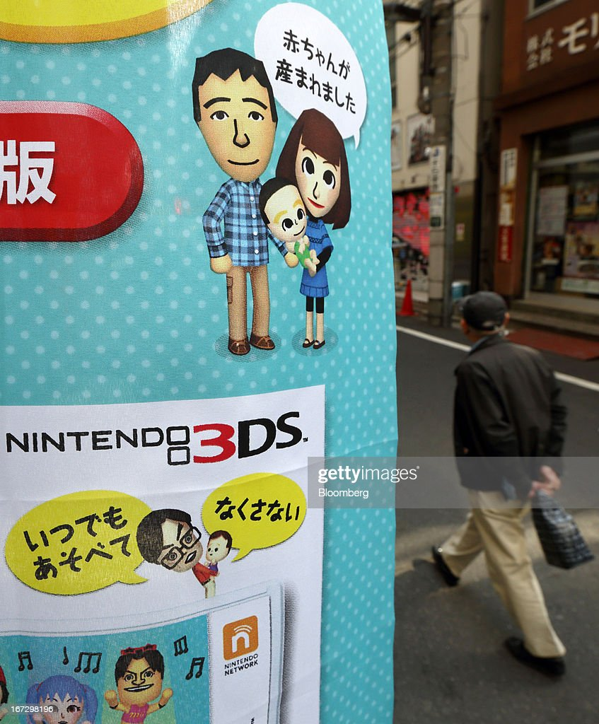 A pedestrian walks past an advertisement for a game title for Nintendo Co.'s 3DS handheld game console outside a convenience store in Tokyo, Japan, on Tuesday, April 23, 2013. Nintendo, the world's largest maker of video-game machines, will announce earnings on April 24. Photographer: Tomohiro Ohsumi/Bloomberg via Getty Images