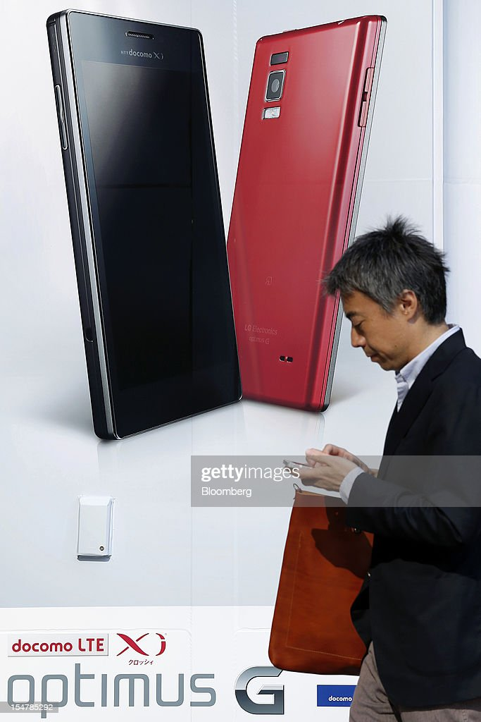A pedestrian walks past an advertisement for NTT DoCoMo Inc.'s Optimus G smartphone, manufactured by LG Electronics Inc., outside an electronics store in Tokyo, Japan, on Friday, Oct. 26, 2012. NTT DoCoMo, Japan's largest mobile-phone company, cut its annual profit forecast 9 percent after competitors lured customers with Apple Inc.'s iPhone 5. Photographer: Kiyoshi Ota/Bloomberg via Getty Images