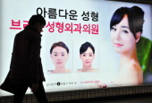 A pedestrian walks past an advertisement for plastic surgery clinic at a subway station in Seoul on March 26 2014 The South Korean capital Seoul is...