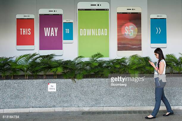 A pedestrian walks past an advertisement for Singapore Telecommunications Ltd in Singapore on Monday Feb 29 2016 Singapore's Infocomm Development...