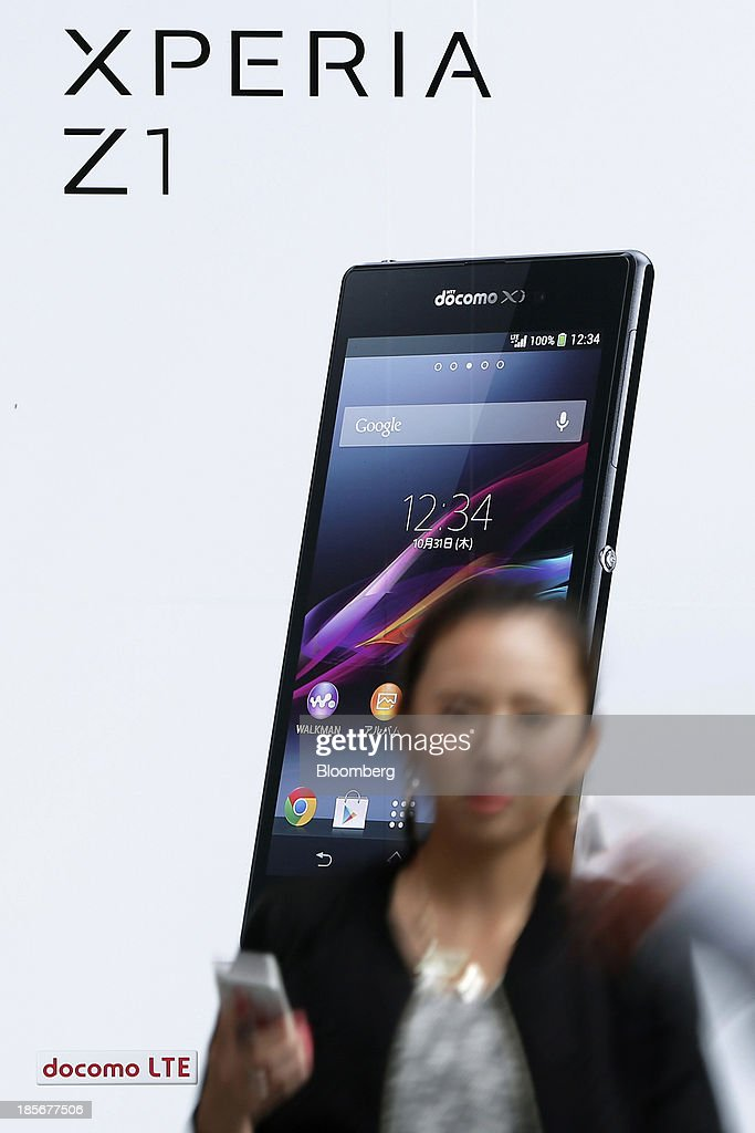 A pedestrian walks past an advertisement for Sony Corp.'s Xperia Z1 smartphone for NTT Docomo Inc. displayed outside an electronics store in Tokyo, Japan, on Wednesday, Oct. 23, 2013. DoCoMo, Japan's largest mobile phone carrier, is scheduled to release earnings results on Oct. 25. Photographer: Kiyoshi Ota/Bloomberg via Getty Images